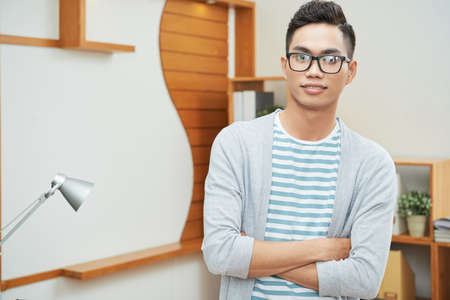 Casual young Asian man in black glasses standing with arms crossed looking at camera in office