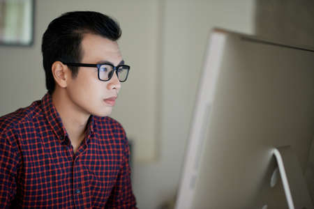 Young Vietnamese programmer working on computer in office