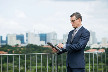 Serious mature businessman using application on tablet computer Imagens
