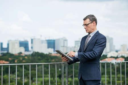 Serious mature businessman using application on tablet computer 版權商用圖片