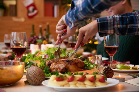 Hands of woman cutting chicken at Christmas dinner table Stock Photo