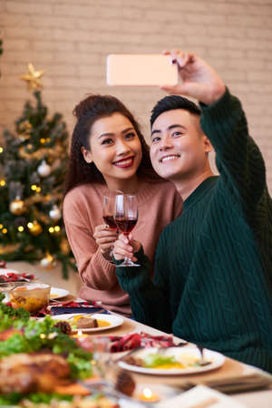 Cheerful young Asian couple photographing together at Christmas dinner table