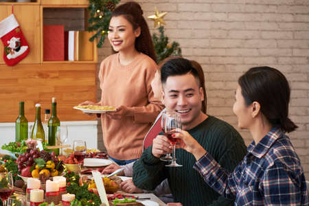 Vietnamese young people talking, eating and drinking wine at Christmas dinner table