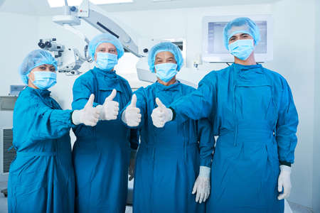 Asian surgical team in masks and uniform looking at camera and showing thumb-up gesture while standing in operating theatre together