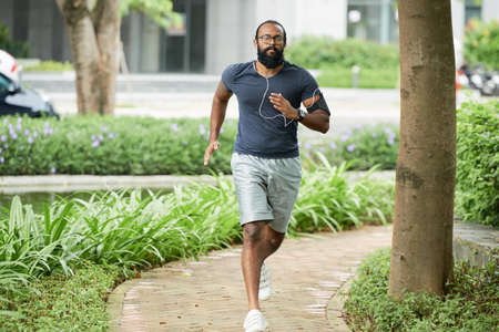 Indian male athlete with long beard and glasses running outdoors and listening to music through earphones Archivio Fotografico