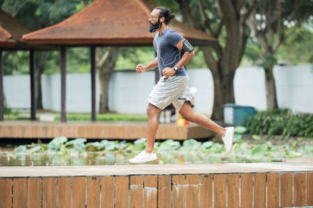 Side view of muscular Indian male athlete with long beard running in the park and listening to music with earphones