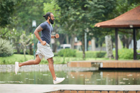 Side view of athletic bearded tattooed Indian man jogging in the morning outdoors and listening to music with earphones