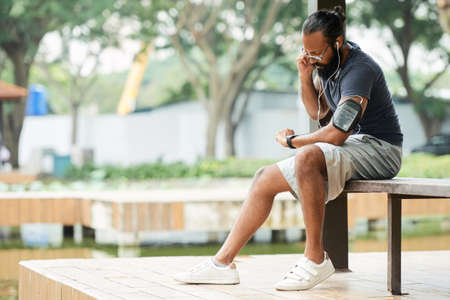 Bearded Indian sportsman looking at watch and taking his pulse after running while sitting on bench outdoors Stock Photo
