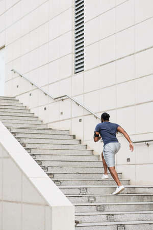 Rear view of unrecognizable sportsman with smartphone on shoulder running up concrete steps while having morning workout Archivio Fotografico