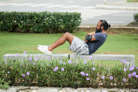Bearded Indian male athlete doing abs exercises while lying on bench in the park and listening to music through earbuds