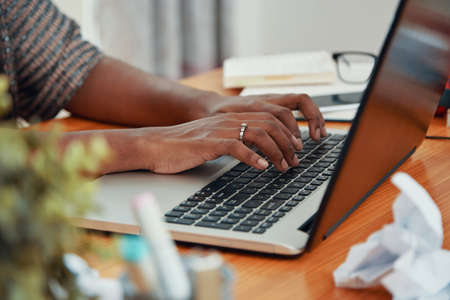 Faceless shot of modern black businesswoman working on laptop and typing on keyboard at table in office