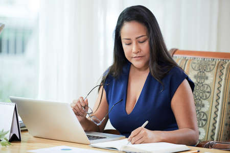 Confident adult Thai woman with glasses sitting at desk in office working with notepad