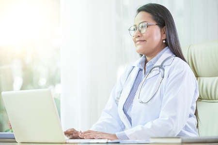 Cheerful Asian woman in doctor coat sitting at desk with laptop working in office of clinic smiling to patient