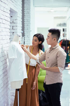 Tailor and designer discussing the model of white shirt while standing in workshop
