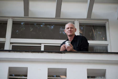 Low angle view of good-looking confident mature Caucasian man standing on balcony with cup of coffee and smiling at camera