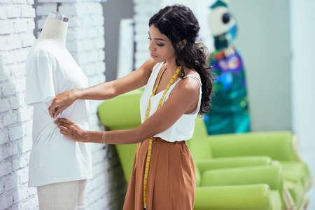 Female dressmaker working on new model tailoring dress on mannequin in studio