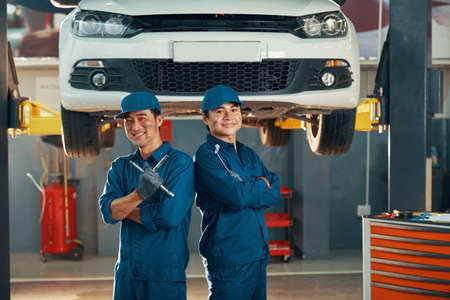 Portrait of two happy auto mechanics in uniforms working in auto service with car in the background