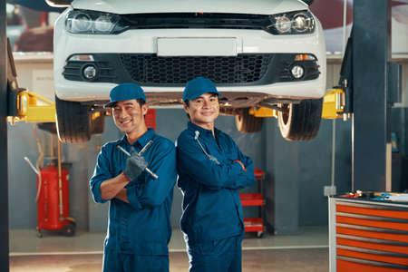 Portret dwóch szczęśliwych mechaników samochodowych w mundurach pracujących w serwisie samochodowym z samochodem w tle
