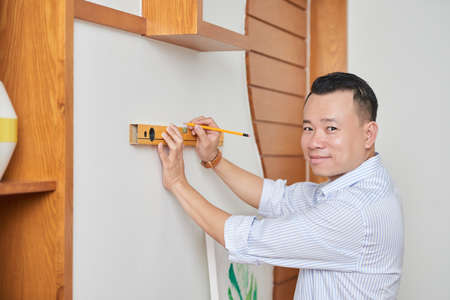 Portrait of Asian smiling designer measuring on the wall with a level and marking the pencil