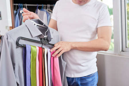 Close-up of man holding his favourite shirt and rack with colorful ties, he choosing the suitable tie Stock Photo