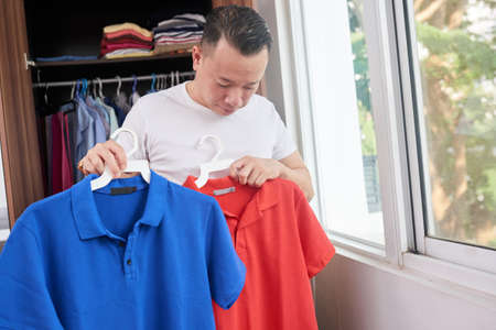 Man standing in his room near the closet and holding two colorful shirts in his hands and trying to choose one