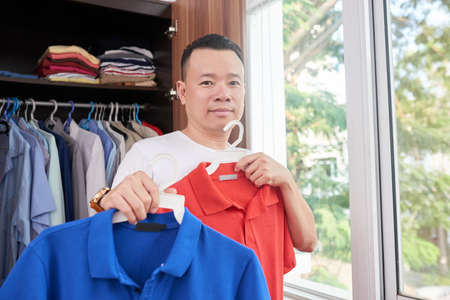 Young Asian man choosing casual style shirt or T-shirt in closet for dressing up in bedroom