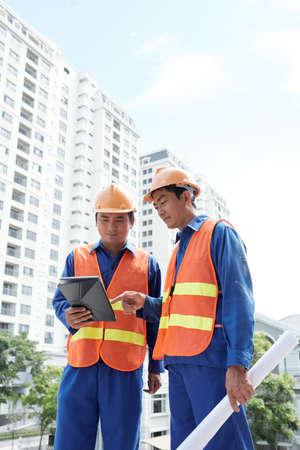 Engineers analyzing data on digital tablet