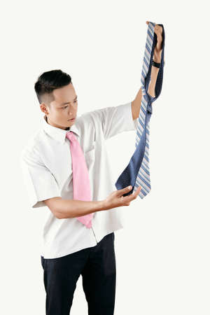High angle view of young Asian man holding ties and picking between them with puzzled face expression on white background Imagens