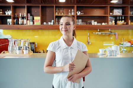 Smiling young woman in white shirt holding clipboard standing in modern coffee shop and looking away