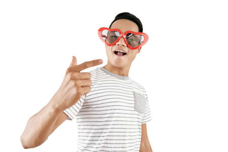 Portrait of young handsome Asian man wearing trendy heart-shaped sunglasses posing on camera against white background