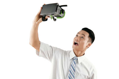 Young Asian male white collar worker making funny faces while playing with head-mounted display against white background Stock Photo