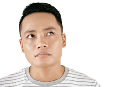 Waist-up portrait of young attractive Asian man looking up thoughtfully against white background, copy space