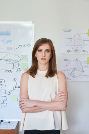 Beautiful confident woman standing with arms crossed in office looking at camera