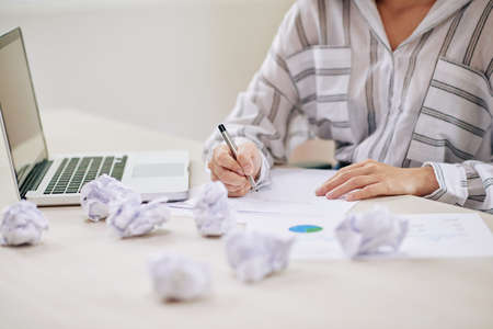 Crop shot of woman making letter and writing on paper while sitting with laptop at desk