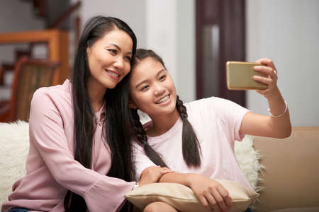 Beautiful Asian adult woman with charming teen girl sitting on sofa and taking selfie with phone Фото со стока