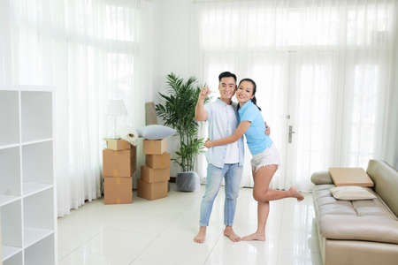 Content embracing Asian couple standing in light room of new modern apartment showing keys Banco de Imagens