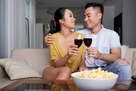 Happy Asian couple embracing on sofa having bowl of popcorn and clinking with wineglasses
