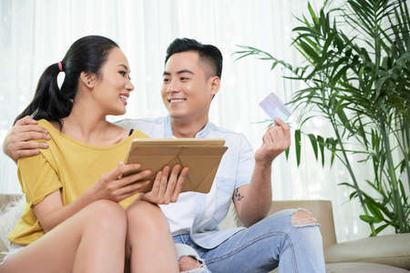 Young loving Asian woman and man holding credit card and using tablet while chilling on sofa at home