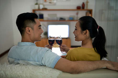 Back view of flirty Asian woman and man clinking with wineglasses on couch at home