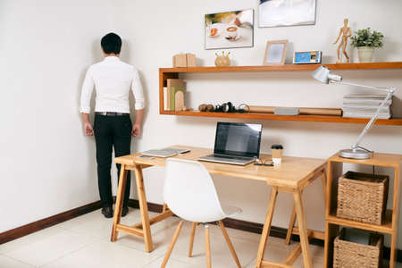 Rear view of businessman standing in the corner of room near his workplace at office, he's guilty of his work Imagens