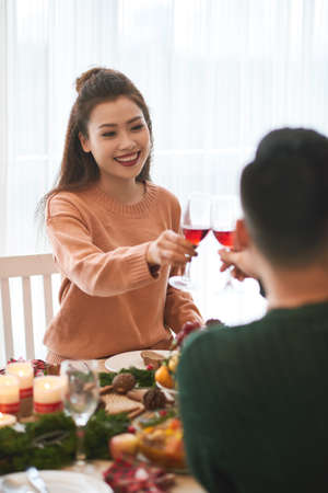 Beautiful young Vietnamese woman and her boyfriend drinking wine at Christmas dinner table