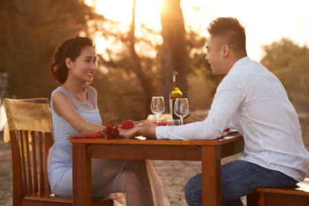 Junges vietnamesisches Paar beim romantischen Abendessen am Strand