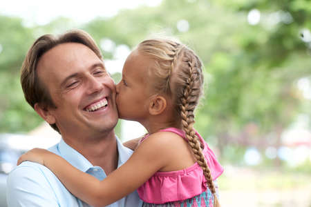 Little girl kissing her laughing father on cheek