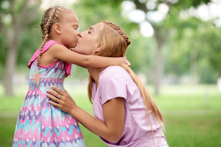 Happy young mother kissing her little daughter in bright suumer dress