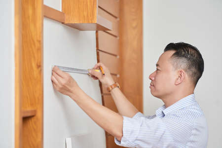 Carpenter measuring wall Stockfoto