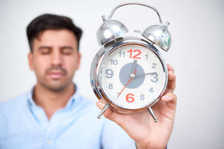 Young man feel sleepy and holding the alarm clock at his hand, its lunch time Stock Photo