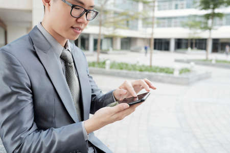 Cropped image of texting young entrepreneur standing outdoors