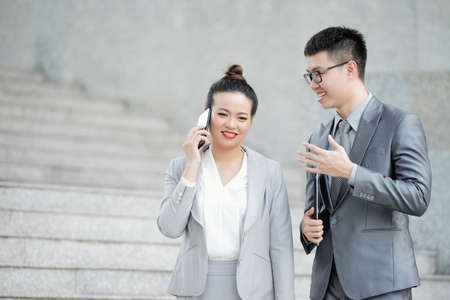 Smiling businesswoman talking on phone when her colleague is giving her advice Stock fotó