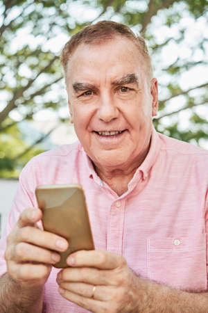 Aged man with smartphone Imagens