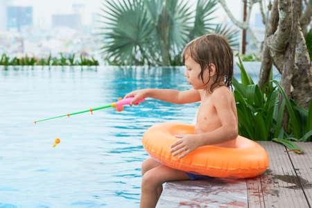 Boy fishing in pool